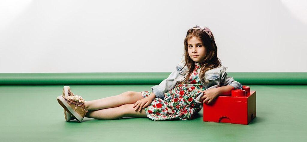 Egy kislány hajdísszel és barna cipőben