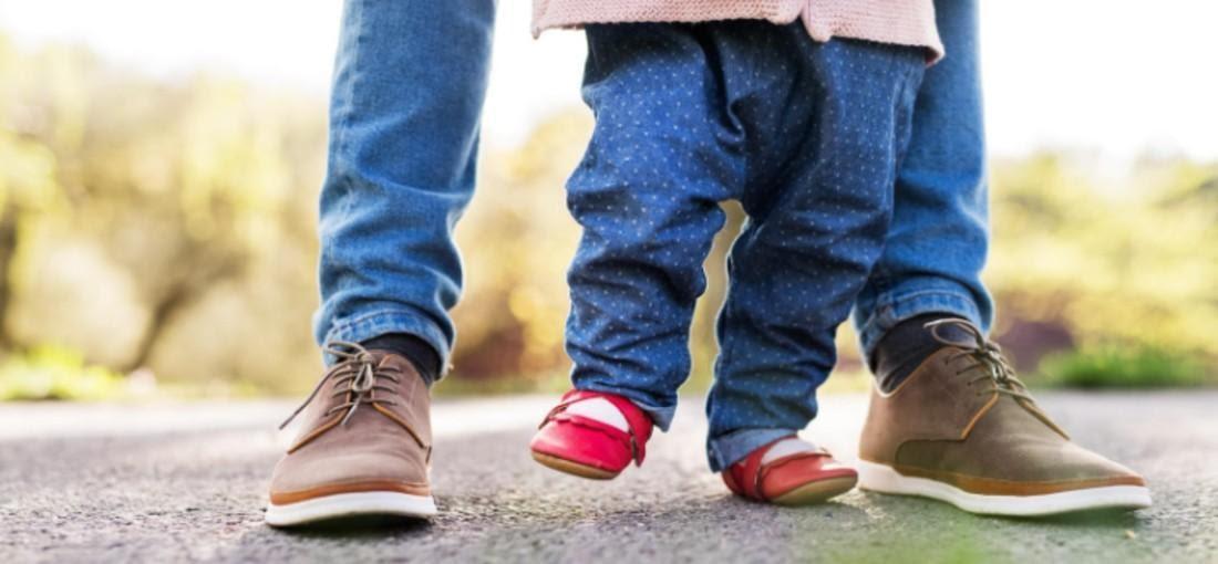 Szülő gyermekével piros és barna cipőben