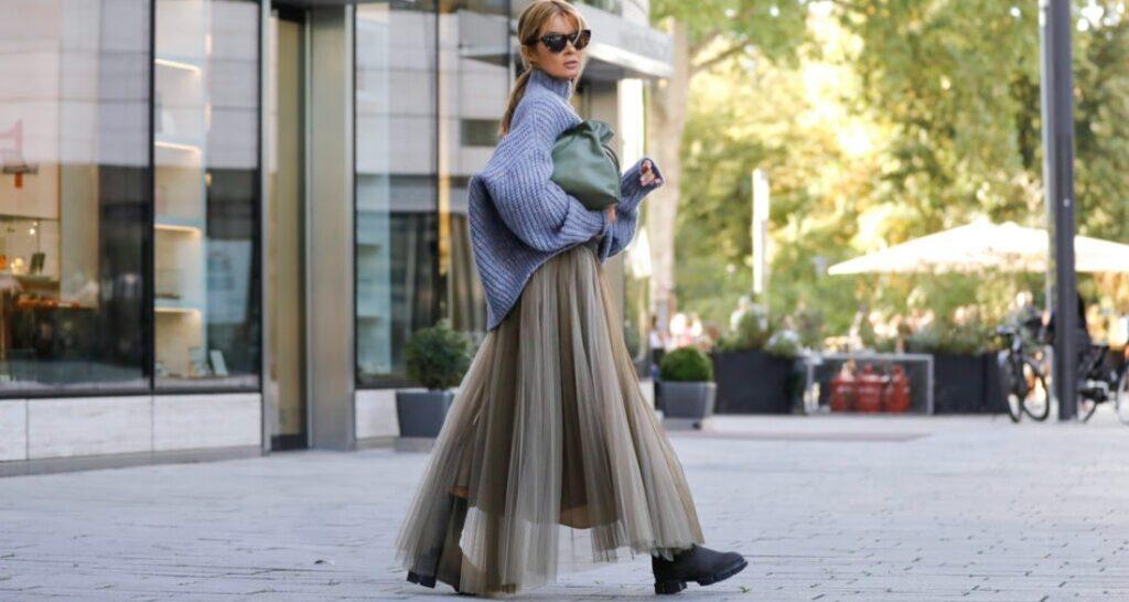 Egy modell kötött pulóverben és szürke-bézs tüllszoknyában